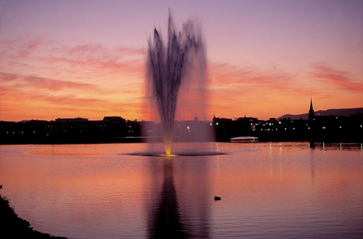A fountain in the pond in Reykjavik at sunset. Iceland
