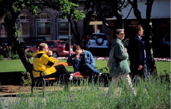 People walking and sitting on a bench somewhere in Reykjavik in summertime