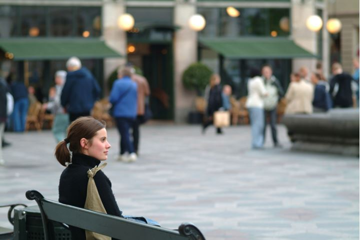A young woman sitting on a bench, more people and a building in background