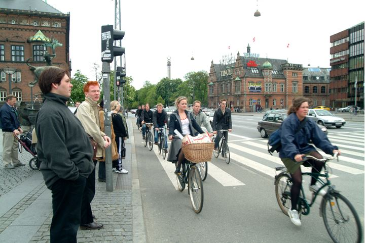 Pedestrians waiting to cross a street while people on bicycles goes by, Copenhagen