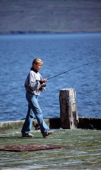 A young, blonde girl with a fishing rod on a dock