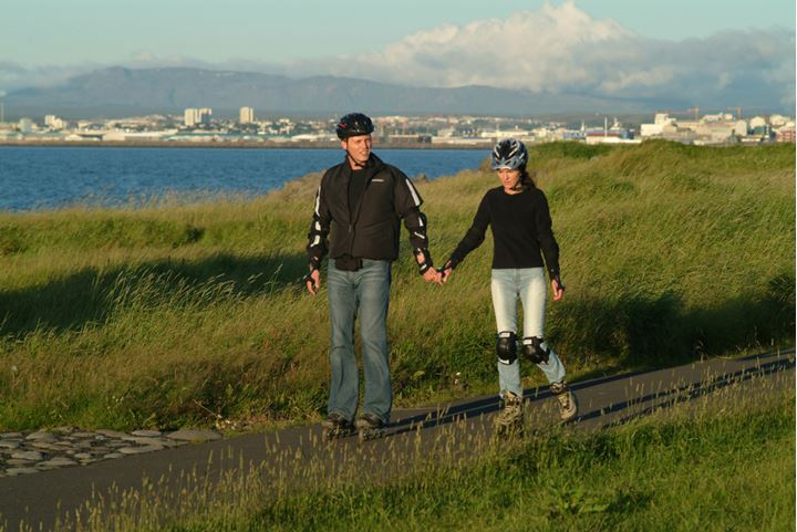 A couple on rollerblades, sea and houses of Reykjavik in background
