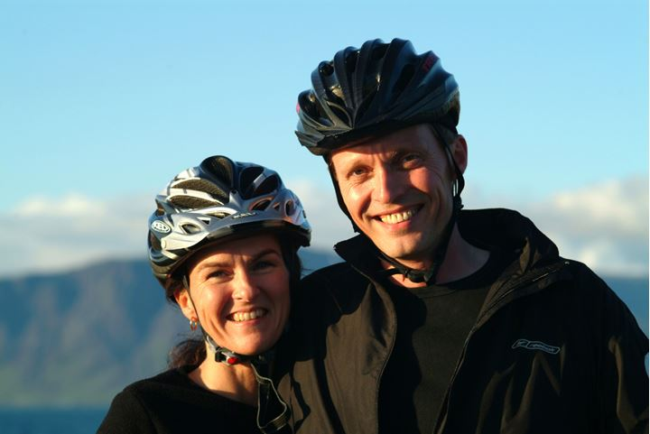 A couple wearing helmets smiling at camera in sunny weather