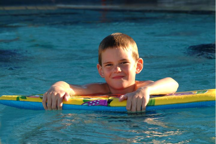A little boy in a swimming pool, looking at camera