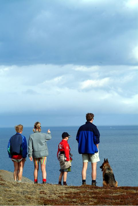 People and a dog standing upon a hill and looking over the sea, cloudy sky above