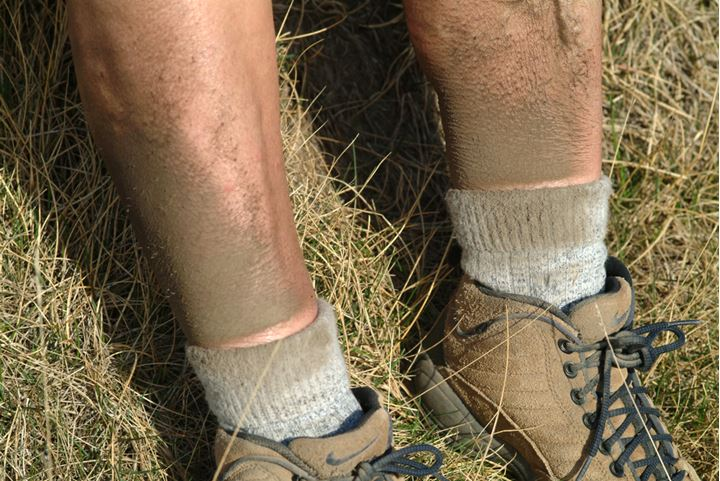 A persons very dirty legs wearing hiking boots