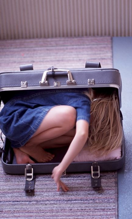 A girl lying in an open suitcase