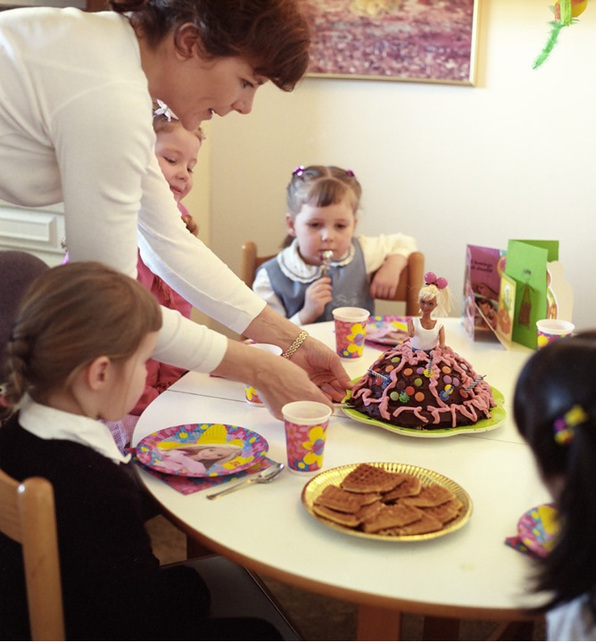 A mother putting a cake on the table at a birthdayparty, children sitting by the table