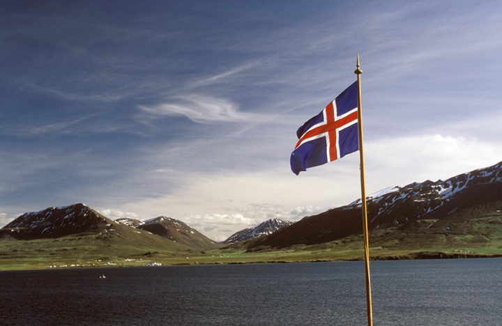 The Icelandic flag, the sea and mountains in background