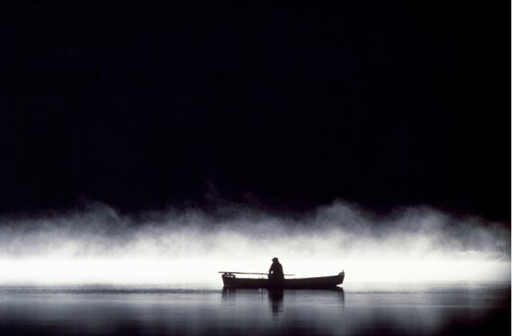 A person in a rowboat on a lake, mist lying over the water
