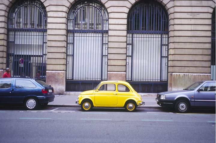 A yellow Fiat in the front of a building