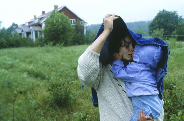 A woman holding her jacket over her baby