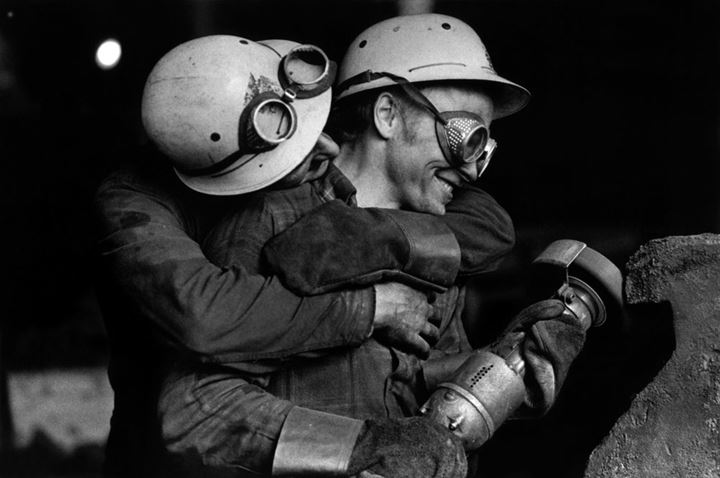 A worker embracing another worker