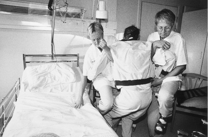 Two nurses assisting a patient in bed