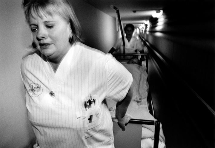Two nurses with a hospital bed in the hallway