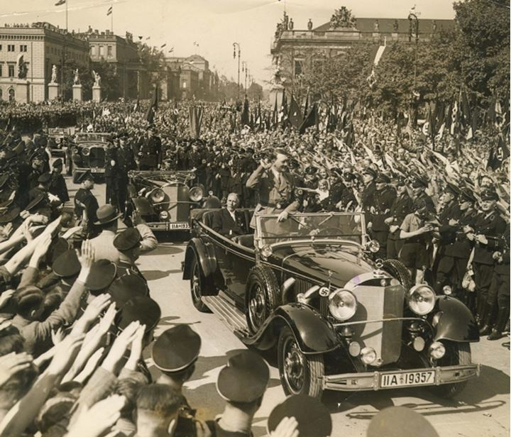 Adolph Hitler drives by crowds who salute