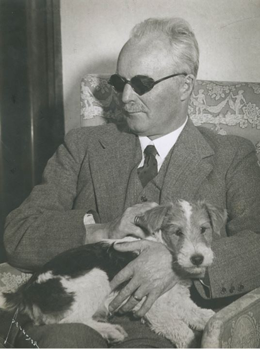 Portrait of a man holding a dog
