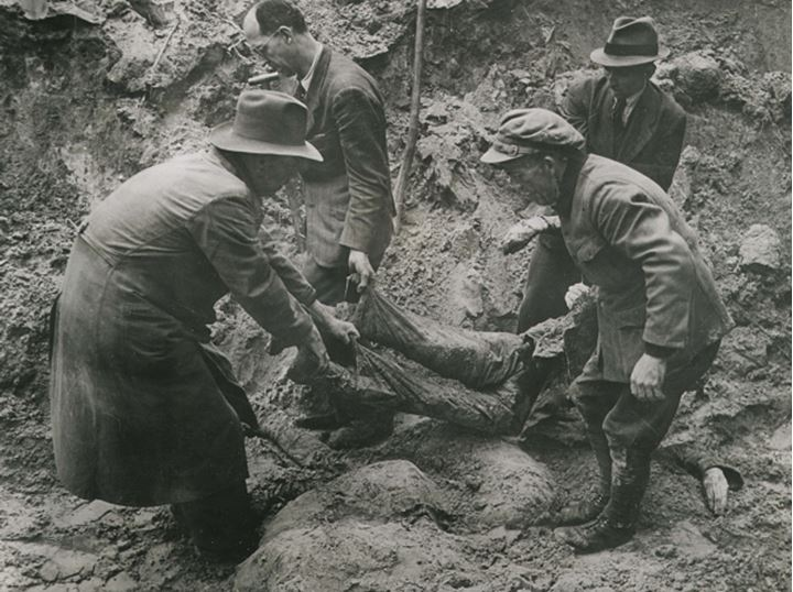People removing bodies from a mass grave