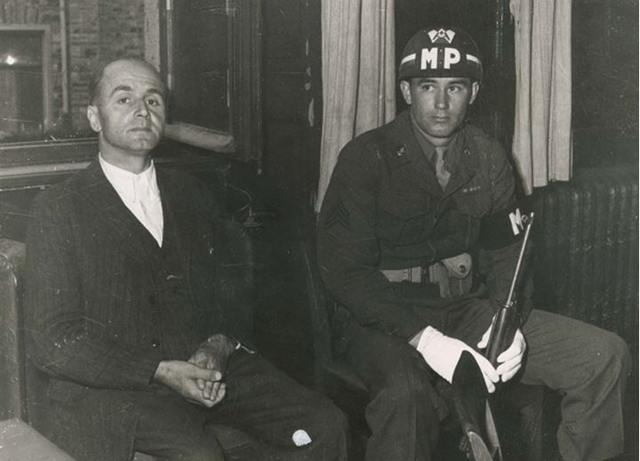 A soldier sits next to another man