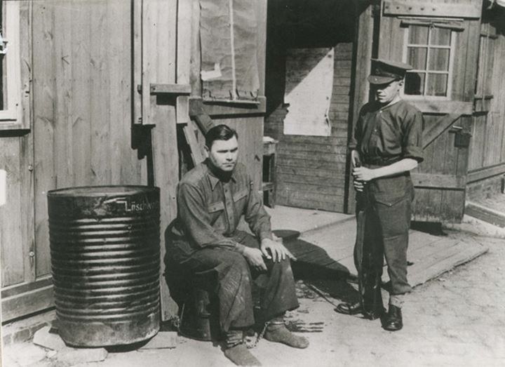 A soldier stands near another sitting on a barrel
