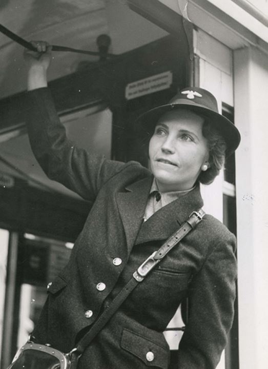 A woman in uniform hanging from a handhold