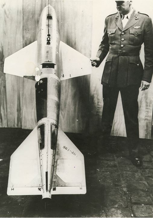 A man stands next to a winged bomb