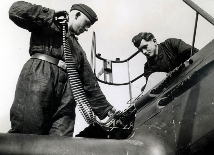 Two men loading ammo to a fighter plane