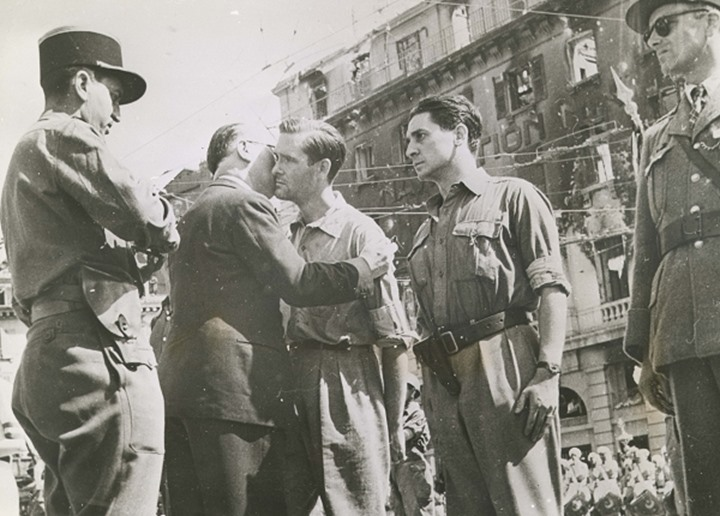 Soldiers standing around outside watch a man kiss another