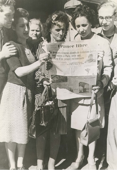 A group of people gather to read a newspaper