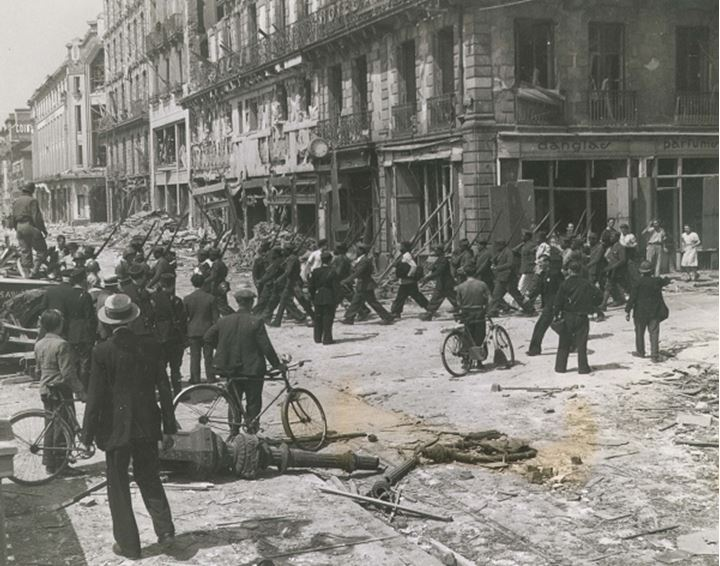 A group of people watch soldiers march by on city street