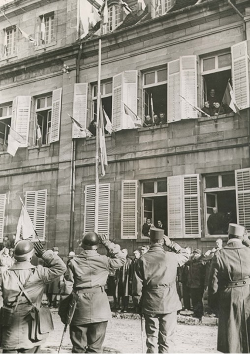 Soldiers salute people at windows