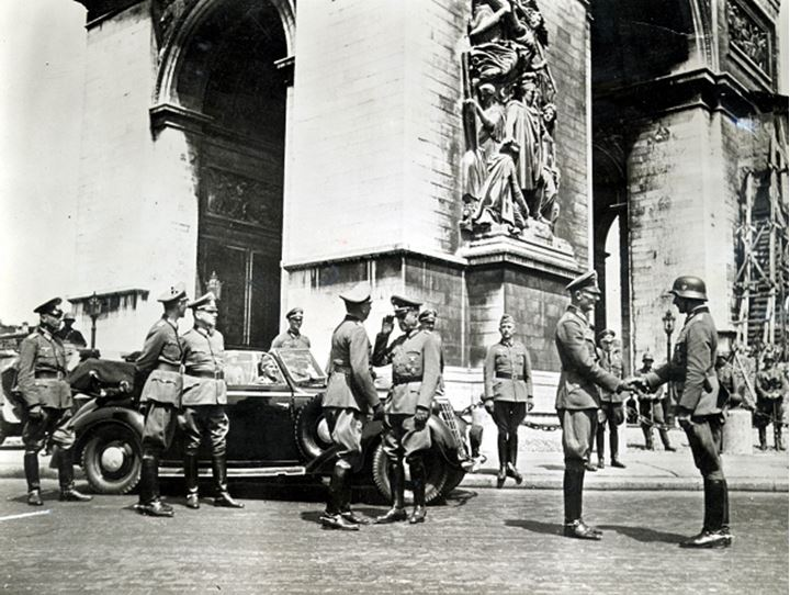 A group of soldiers gathered around a monument
