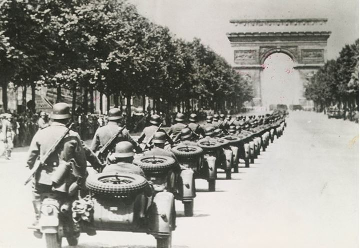 A line of soldiers on motorcycles ride into France