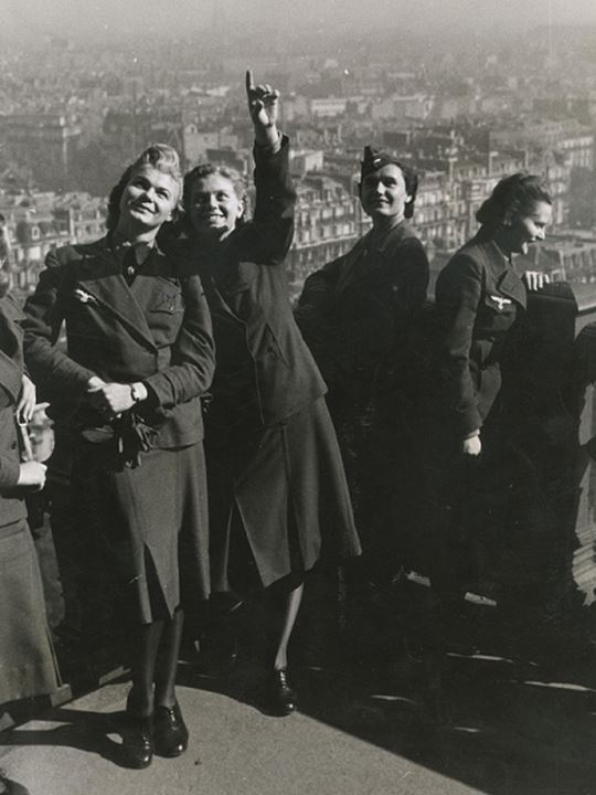 Smiling women point to the sky