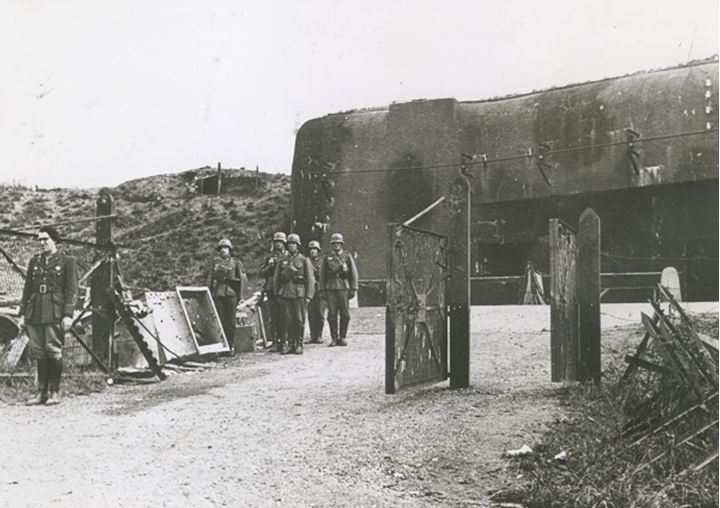 A group of soldiers standing guard outside a bunker