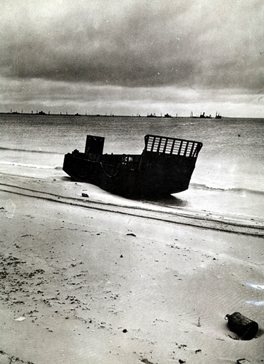A landing craft silhouetted on the beach