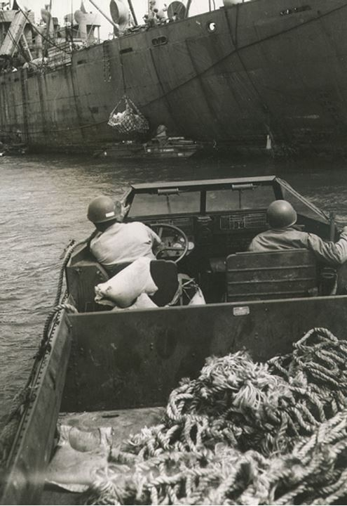 Soldiers drive a smal boat towards a warship