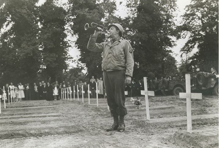 A soldier blows a bugle in a cemetary