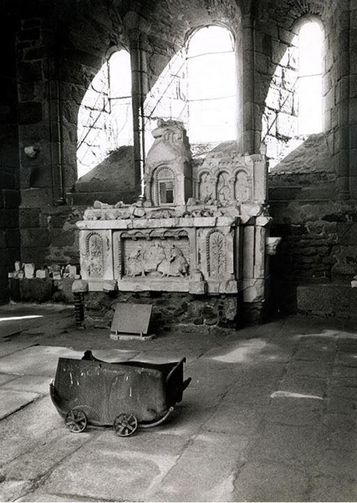 A baby carriage sits before an altar