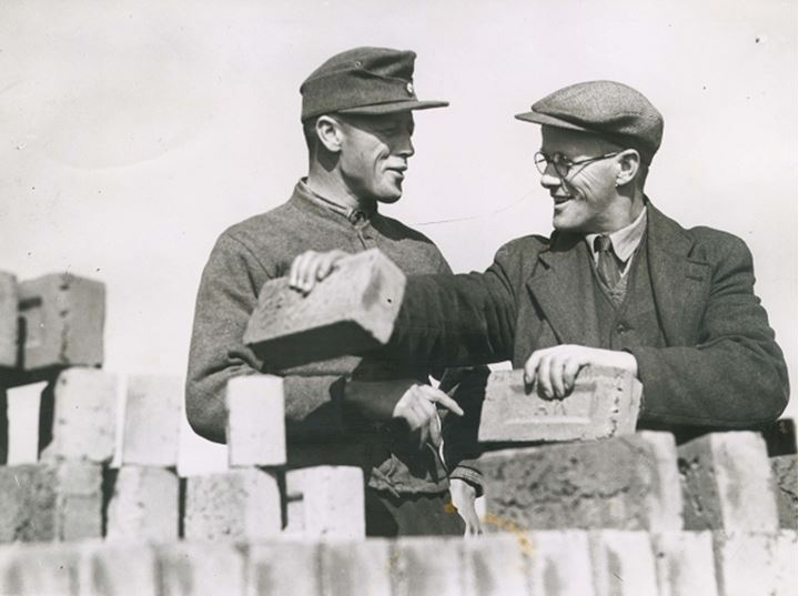 Two men laying bricks on a wall