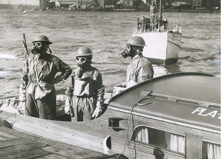 Soldiers in gasmasks riding on a boat
