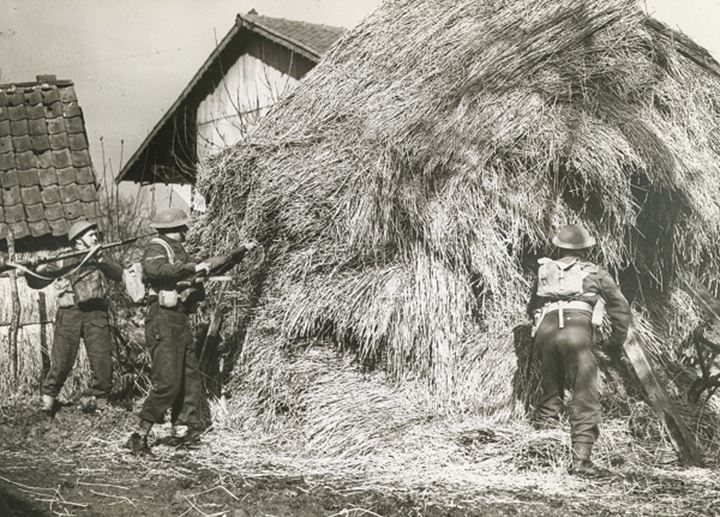 Soldiers poking at a haystack with bayonets