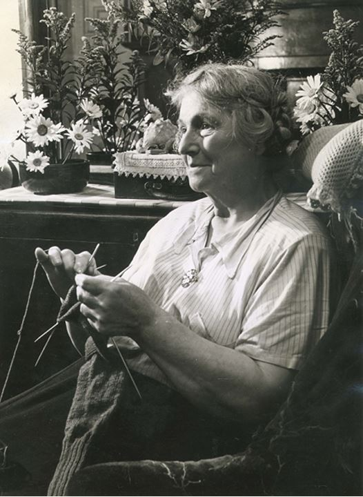 An older woman sits knitting