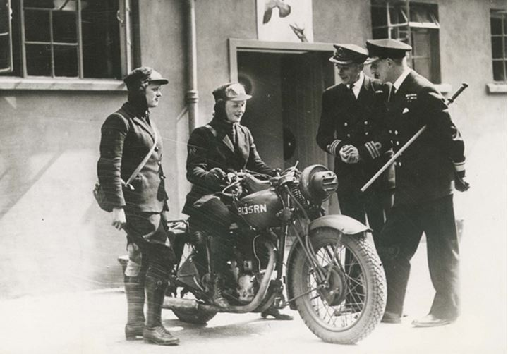 A group of men talking to a woman on a motorcycle