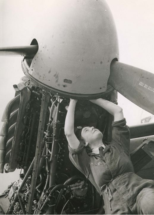 A female mechanic works on an airplane engine