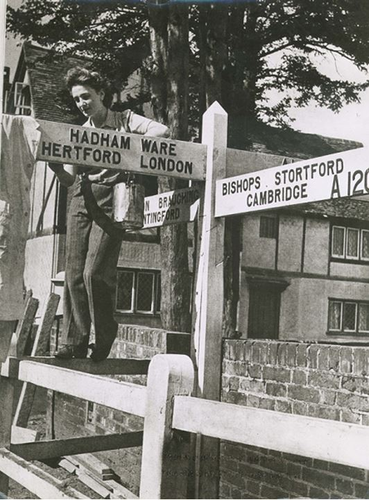 A woman poses standing on top of a fence at an intersection
