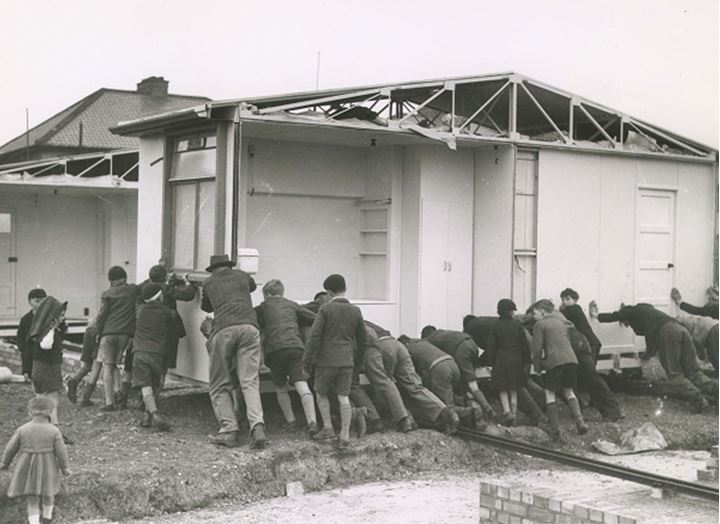 A group of men and boys labor to push a house on rails