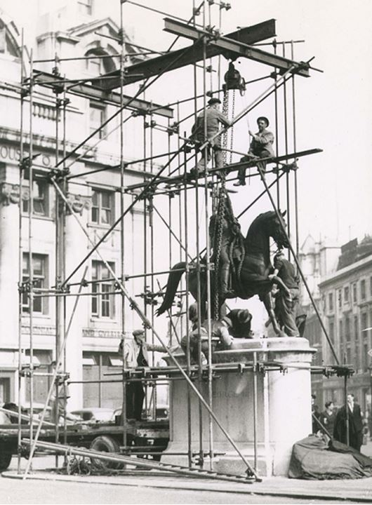 Workers work on scaffolds erected over a statue