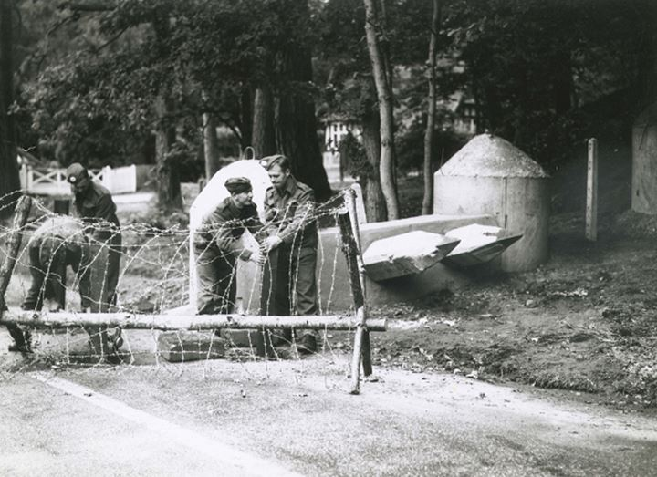 Soldiers work to assemble a barbed wire barricade