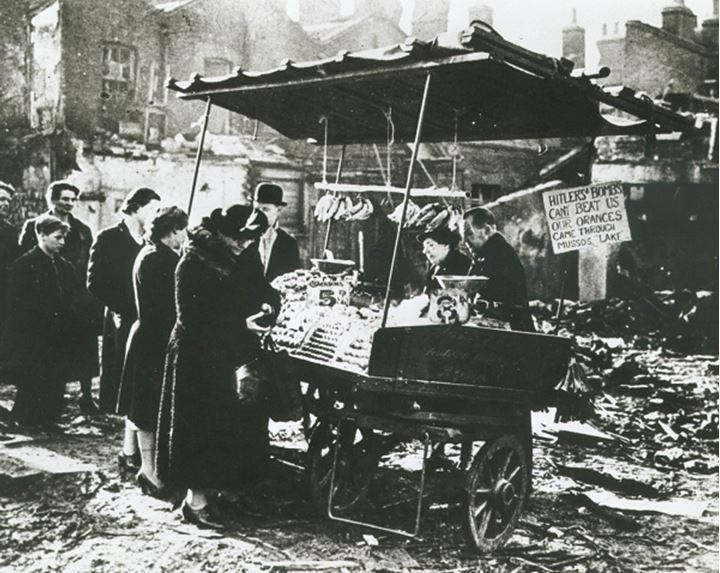 People line up to buy food from a cart amidst ruins